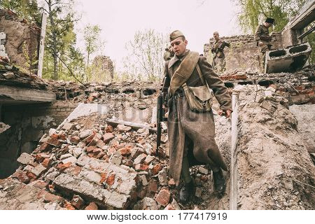Pribor, Belarus - April 24, 2016: Re-enactor Dressed As Soviet Russian Red Army Infantry Soldier Of World War II Is Performing Mopping-up Operation With Submachine Gun Along Rubble Of Building