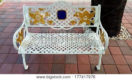 White bench in garden and background .