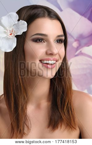 Dreaming of spring. Vertical studio shot of a beautiful young female smiling looking away wearing white orchid flower in her hair seasonal spring flowers floral natural beauty cosmetology treatment