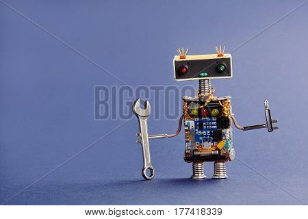 Robot serviceman with hand wrench and screwdriver on blue background. Abstract mechanical toy worker made of electronic circuits, chip capacitors vintage resistors.