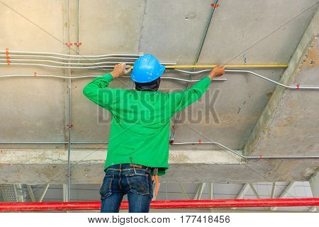 Construction worker measuring with metal pipes electrical distribution system with measuring tape in new building