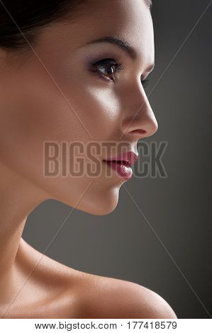 Organic beauty. Close up profile shot of a beautiful woman with flawless skin looking away on grey background face lips eyes nose skincare healthy cosmetics treatment salon procedure concept