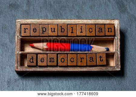 Republican democrat politic alternative choice concept. Vintage box, wooden cubes phrase with old style letters, red blue colored pencil. Gray stone textured background. Close-up, up view, soft focus