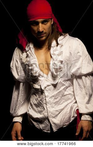 Sexy guy dressed as pirate against dark background