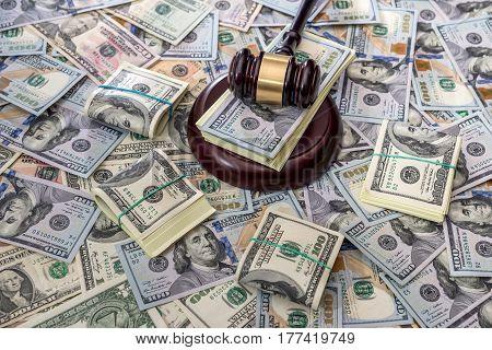 Auction concept - judges gavel against us dollar background.