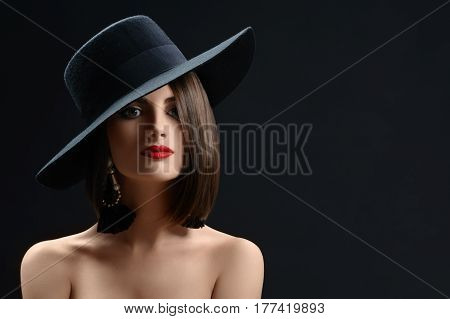 Studio portrait of a beautiful red lipped brunette female wearing a hat posing on black background copyspace elegance style class luxury beauty cosmetic mystery femininity concept.