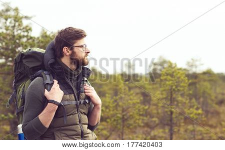 Handsome, bearded guy hiking in swamps and enjoying the views. Camp, adventure, trip and fishing concept.