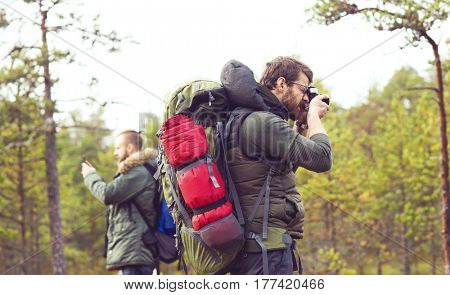 Two guys with backpacks walking in swamps and taking pictures. Camp, adventure, traveling and fishing concept.