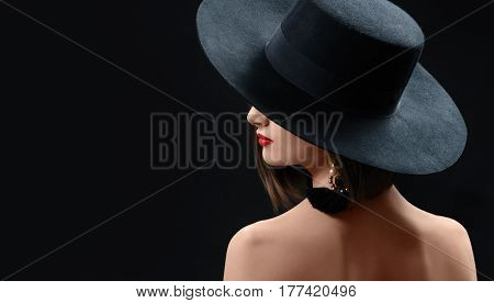 Rearview shot of a mysterious sexy red lipped brunette woman in a hat posing gracefully on black background looking at the copyspace over her shoulder beauty skin perfection secrecy incognito hide.