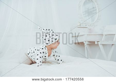 Newborn Baby Dressed In A White Suit And Black Stars Is A White Soft Bed In The Studio