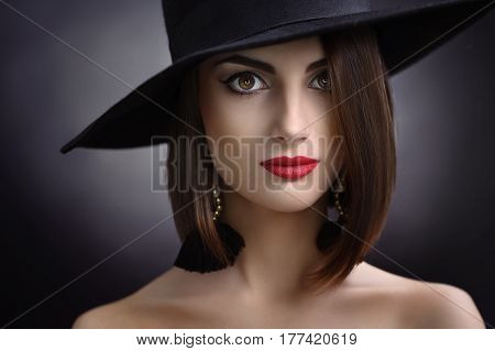 Close up studio beauty portrait of a gorgeous red lipped young brunette wearing a wide hat smiling to the camera on black background beauty cosmetics skincare confidence retro vintage.