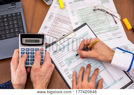 two people filling tax forms helping each other.