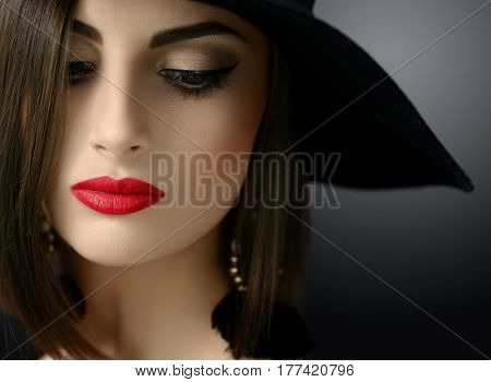 Cropped close up of a sexy red lipped young dark haired woman in a hat posing looking away sensually sexuality femininity beauty face cosmetics makeup fashion style retro vintage concept.