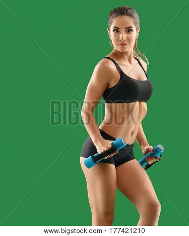 Focusing on sports. Beautiful sporty young woman in top and shorts exercising with dumbbells smiling joyfully showing off her toned sexy hot body on green background gym lifestyle training wellness