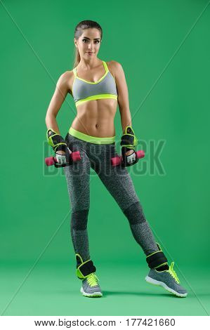 Shape up Vertical full length shot of a gorgeous young fitness model smiling posing in her workout gear exercising with dumbbells on green background gym strength power motivation body sexy hot .