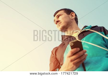 sportsman looking far away and listening music with phone in his hand