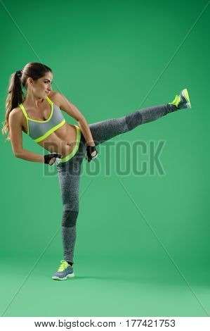 Getting fit. Vertical portrait of a young strong fitness woman wearing sports gear performing high kick training at studio on green background workout exercise kickboxing defense strength sportswoman