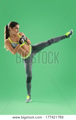 Got fight inside. Vertical studio shot of a young sportswoman with toned strong body training performing kick on green background fitness kickboxing karate defense power strength confidence fighter