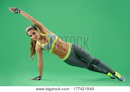 Stretch your body Studio shot of a beautiful fitness woman in workout gear doing plank exercise stretching out her arm smiling happily on green background exercising training practicing yoga gym.