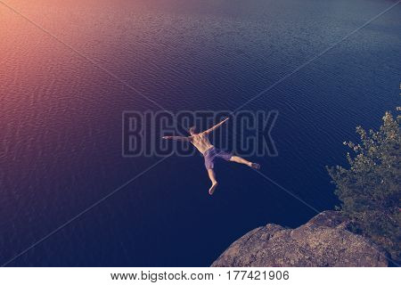 Young man jumping into the lake from cliff