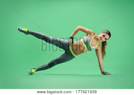 Working on her legs. Young sporty woman doing side planking workout raising her leg on green background gym fitness yoga workout exercise trainer body dieting healthy happiness vitality