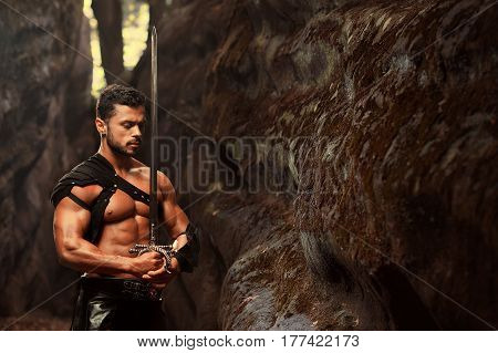 Deep in his thoughts. Horizontal portrait of well-built muscular young warrior standing with a sword with his eyes closed near the rock at the woods