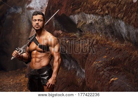 Portrayal of strength. Portrait of a strong handsome gladiator standing with a sword outdoors copyspace