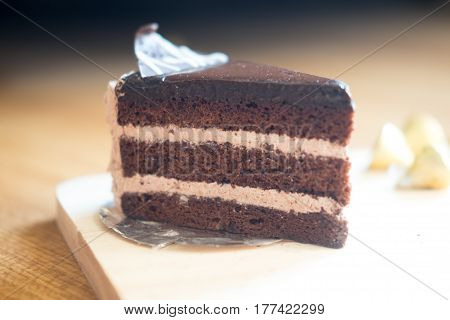 Slice of chocolate cream cake on wood table selective focus