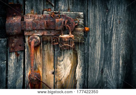 Old rusty padlock on wooden door. Home security