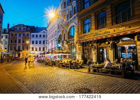 Riga, Latvia - July 1, 2016: People Resting In Street Cafe Restaurant In Old Town Under Facades Of Old Architectural Buildings. Evening Or Night Illumination In Old Town In Tirgonu Street