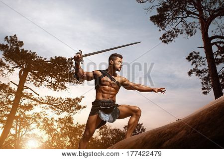 Graceful masculinity. Young muscular warrior with a sword lurking carefully in the woods at the dusk copyspace