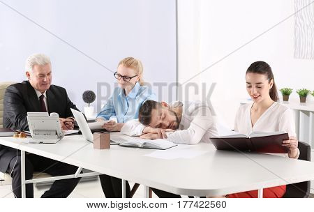 Tired young man sleeping during conference in office