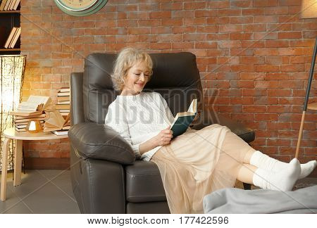 Happy senior woman sitting in armchair and reading book