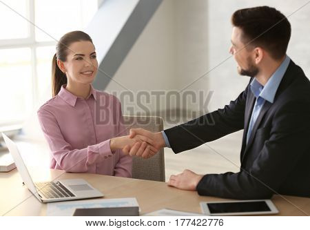 Manager and client shaking hands in office