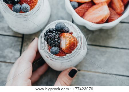 Top View Of Woman Hands With Pudding With Chia Seeds, Yogurt And Fresh Fruits: Strawberries, Blueber