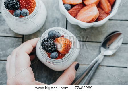 Woman Hands With Pudding With Chia Seeds, Yogurt And Fresh Fruits: Strawberries, Blueberries And Bla