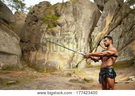 Practicing his skills. Horizontal shot of a masculine Spartan warrior practicing with a sword near the rocks