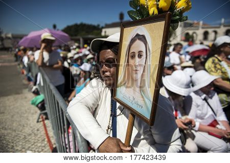 Fatima Portugal - May 13 2014: Woman holding a image at the Sanctuary of Fatima during the celebrations of the apparition of the Virgin Mary in Fatima Portugal.