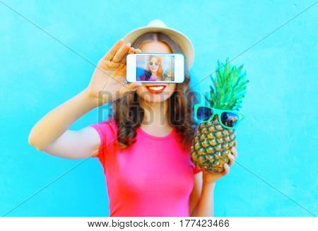 Fashion Woman With Pineapple Taking Picture Self Portrait On Smartphone Over Colorful Blue Backgroun