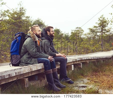 Two brutal, bearded men with backpacks sitting in swamps. Camp, adventure, traveling and trip concept.