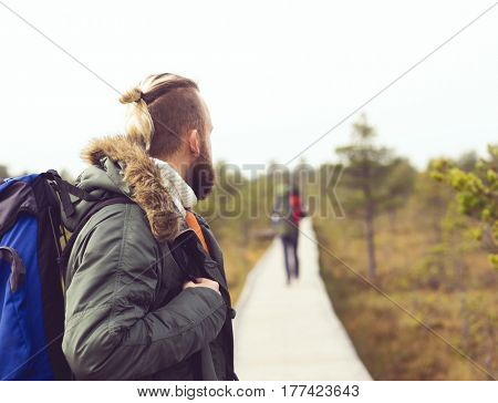 Two bearded guys hiking in swamps in autumn forest. Camp, adventure, trip and fishing concept.