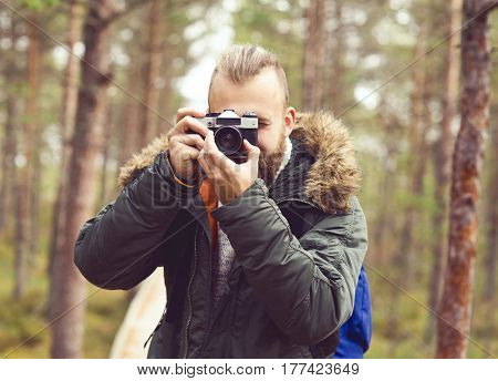 Bearded man hiking in swamps and taking pictures of autumn forest. Camp, adventure, trip and fishing concept.