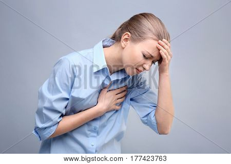 Heart attack concept. Young woman suffering from chest pain on grey background