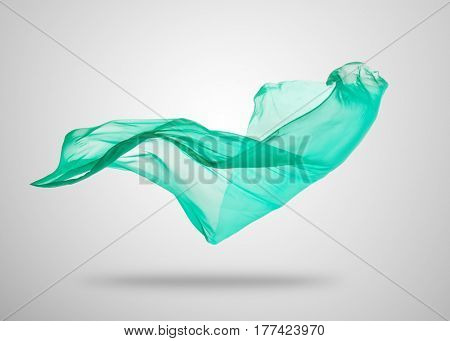 Smooth elegant transparent green cloth separated on gray background. Texture of flying fabric.
