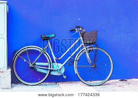 Retro old bicycle standing near blue wall.