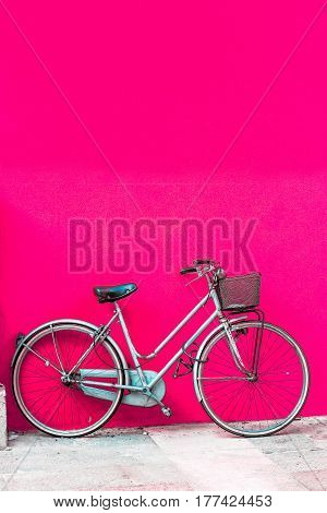 White bicycle standing near empty pink wall.