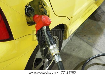 Nozzle fuel Gasoline serving in to the small car The door cover has sticker sign silver Gasohol e20 inside.