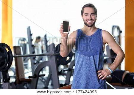 Handsome young man with fitness tracker and mobile phone in gym