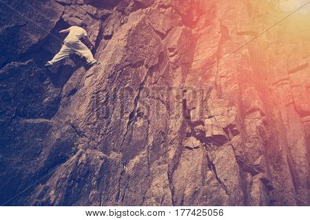 Young risky man climbing over danger mountain without any rope