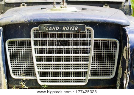 Penang, Malaysia - October 23, 2014: Abandoned old rusty car. Retro background with part of blue bumper with lattice land-rover